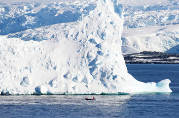 Rubber boat beside huge iceberg. Antarctic Peninsula.