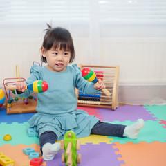 baby girl play maracas at home