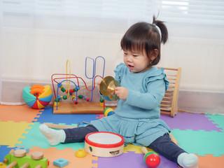 baby girl play cymbals at home