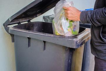 Men putting garbage in garbage bin