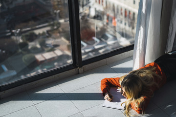 High angle view of young woman sketching on book while lying on tiled floor at home