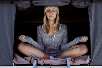 Woman meditating while sitting in roof tent on car