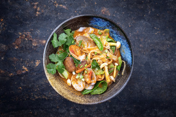 Traditional Thai kaeng phet red curry with clams and vegetable as top view on a plate