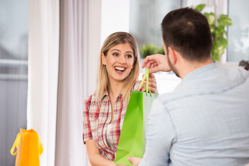 Young couple with shopping bags at home