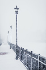 Street lights by metallic railing during snowfall