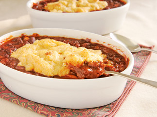 Two bowls of homemade chili with cobbler topping
