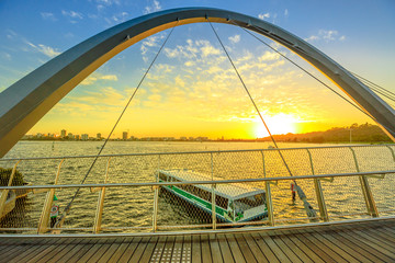 Turistic ferry crossing iconic Elizabeth Quay Bridge at sunset on Swan River. Scenic landscape seen from wooden walkway of arched pedestrian bridge of Elizabeth Quay marina. Perth, Western Australia.