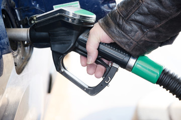 hand holds a nozzle to refuel a car with diesel fuel at the gasoline station