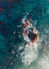 Overhead view of surfers paddling near rocks in ocean