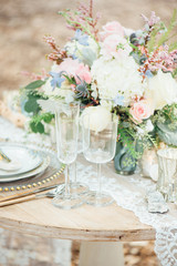 Champagne flutes and bouquet on table outdoors
