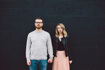 Portrait of couple holding hands against black concrete wall