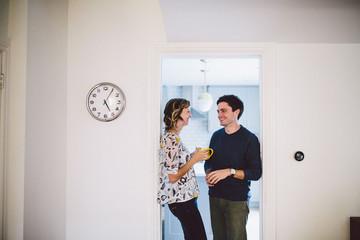 Couple drinking coffee in office doorway