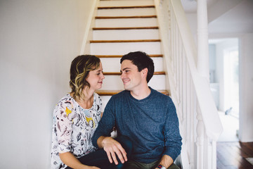 Couple sitting at bottom of staircase at home