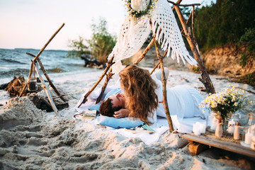 A loving couple spends time together on the seashore. They lie on the sand on the blanket and enjoy each other