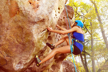 Portrait of woman rock climbing with harness