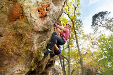 Young girl climbs a rock with harness in woodland