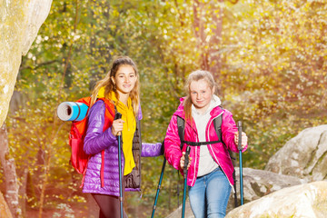 Hikers with trekking sticks at sunny day outdoors