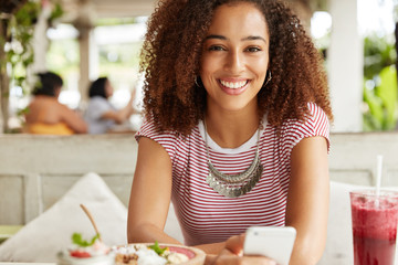 Attractive female model with Afro hairstyle, dark skin and shining smile, watches favourite movie online on smart phone, connected to wireless internet at cafeteria, surrounded with dish and beverage