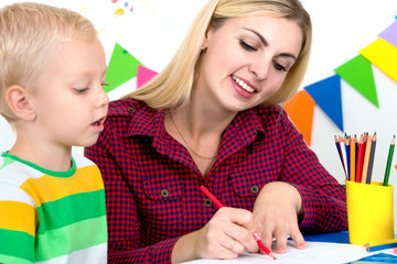 A little boy draws with the mother.Family leisure.