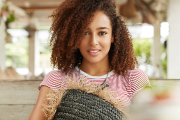 Close up shot of curly young African American woman has gentle smile, rests alone on comfortable sofa with cushion, spends free time with friends at restaurant, has appealing attractive look