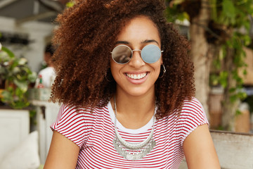 Dark skinned attactive female tourist in sunglasses enjoys summer vacations abroad, visits local cafes and restaurants, happy to taste delicious cuisine, has broad appealing smile. Happiness concept