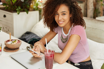 Mixed race black female model work freelance at cafe interior, surrounded with modern technologies and tasty drink. Attractive Afro American female browses information via smart phone online