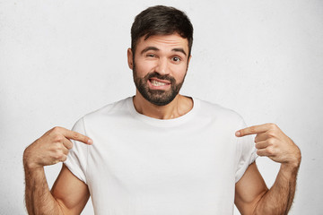 Funny bearded young brunet male with doubtful cheerful expression dressed in casual white t shirt, indicates with fore fingers at blank copy space for your logo, advertisment or promotional text