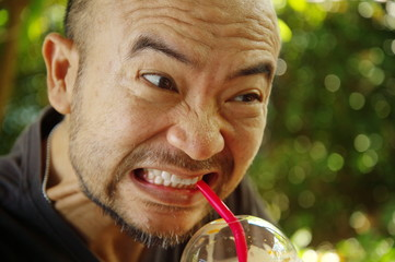 aggressive angry adult bald beard Asian Japanese man bite red straw for drink