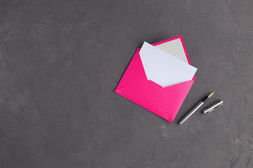 Pink envelope on stone background top view