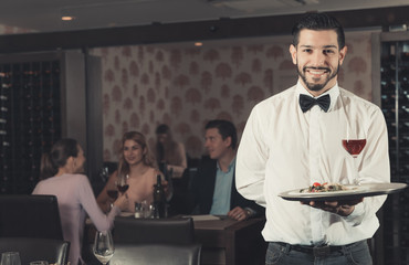 Adult waiter with tray welcoming to restaurant