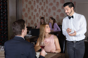 Confident waiter taking order from elegant young pair in restaurant