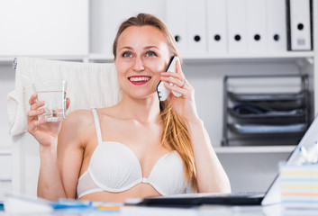 Cheerful woman in bra working
