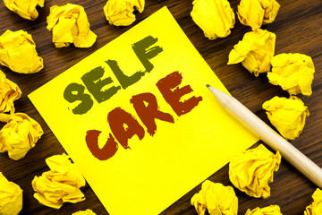 Word, writing Self Care. Business concept for Taking caring for own Health Written on sticky note paper, wooden background with folded yellow paper meaning thinking