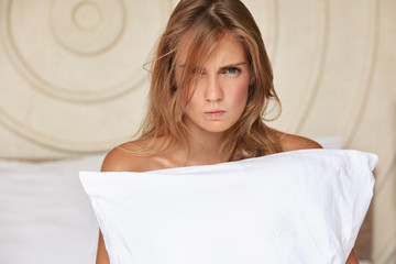 Indoor view of irritated discontent woman with white soft pillow, being annoyed with husband, have family quarrel at bedroom, have spoiled relationships. Displeased young cute female poses indoor