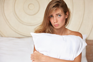 Unappy female model stays in booked hotel room, poses with pillow, has displeased expression as being dissatisfied with service. Pretty woman abused by boyfriend, suffers from betrayal, feels lonely
