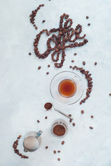 Food lettering in high key drink photography from above. Word Coffee made with coffee beans. Moka pot alternative brewing.