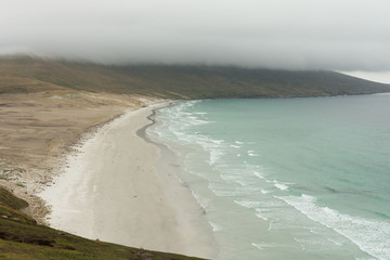 Saunders Island Beach with sweeping off white sand photographed from above. A bank of clouds is in the distance.