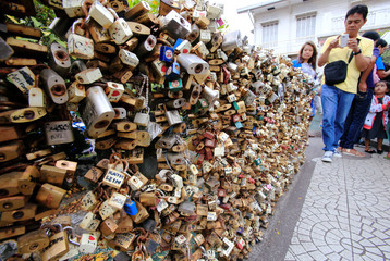 """A man takes a selfie of the """"Love Lock"""" fence, the symbol of undying love with God, near the National Shrine of Our Mother of Perpetual Help in Paranaque city, as part of Valentine's Day celebrations, Metro Manila"""