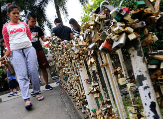 "Passerby looks at ""Love Lock"" fence, the symbol of undying love with God, near the National Shrine of Our Mother of Perpetual Help in Paranaque city, as part of Valentine's Day celebrations, Metro Manila"