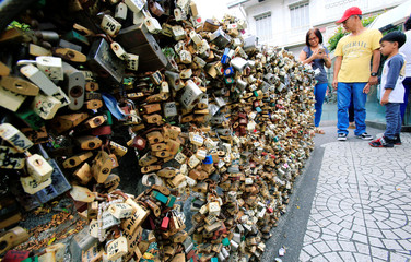 "A couple looks at ""Love Lock"" fence, the symbol of undying love with God near the National Shrine of Our Mother of Perpetual Help in Paranaque city, as part of Valentine's Day celebrations, Metro Manila"