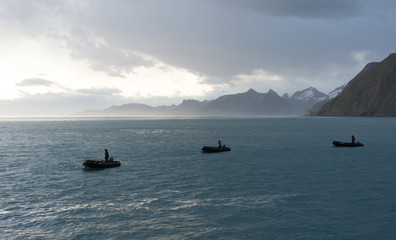 Three Zodiak inflated boats being driven across the blue gray water of the Southern Ocean. Cloudy sky is above.