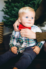 millenial mom putting a red bow tie on her one year-old son