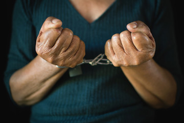 Close-up old hands of woman and chain on black background, Concept no freedom