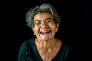 Happy Asian old woman smiling and joyful on black background