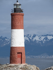 Beagle Channel Lighthouse with snowy Mountains in the Background. The town of Ushuaia is in the distance.
