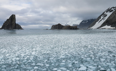 Elephant Island with cloudy skies above and a bay filled with sea ice in the foreground.
