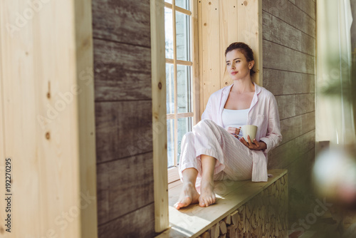 89588e9584f1 thoughtful woman in pajamas holding cup of coffee and sitting on windowsill