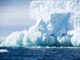 An unusual light blue and aquamarine iceberg with a base of onion-shaped formations and a wall of ice above.