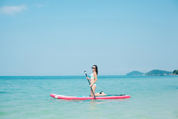 young girl on stand up paddle board on sea at tropical resort