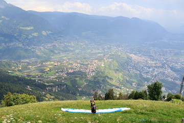 Paragliders prepare for Paragliding in front of Merano panaroma in South Tyrol